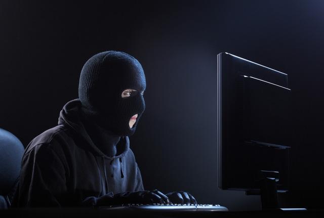 hacker nhìn màn hình máy tính